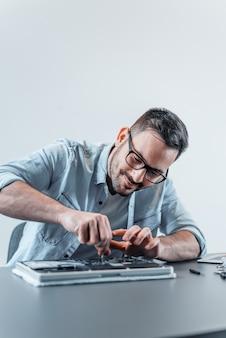 Glücklicher techniker, der laptop-hardware repariert