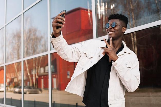 Glücklicher teenager, der ein selfie im freien nimmt