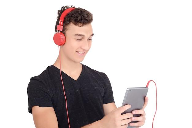 Glücklicher teenager, der tablette mit kopfhörern verwendet