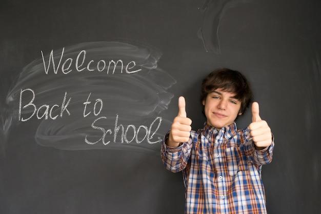 Glücklicher teenager mit zurück zur schule an der tafel