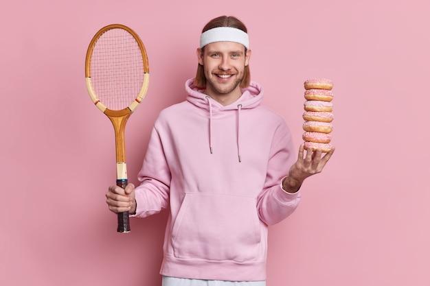 Glücklicher tennisspieler wählt zwischen gesundem lebensstil und schädlichem essen hält schläger und ein haufen süßer donuts trägt sweatshirt und stirnband. europäischer bärtiger mann wird badminton spielen