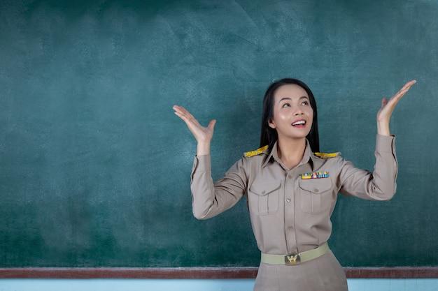 Glücklicher thailändischer lehrer im offiziellen outfit, der vor dem rückenbrett handelt