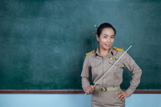 Glücklicher thailändischer lehrer im offiziellen outfit, der vor tafel posiert