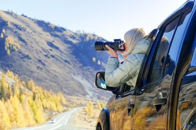 Glücklicher tourist, der in landschaft reist. touristische frau in einem offenen fenster eines selbstautos, das fotografie macht. blogger, der hobbyinhaltskonzept verwendet, genießen reise.