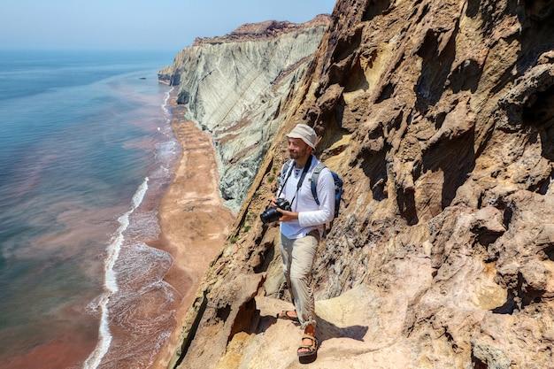 Glücklicher tourist mit kamera steht am rand der klippe, hormuz island, hormozgan, iran.