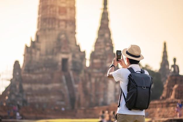 Glücklicher touristenmann mit rucksack, der foto durch mobiles smartphone nimmt, während des besuchs im tempel wat chaiwatthanaram im historischen park ayutthaya, sommer-, solo-, asien- und thailand-reisekonzept