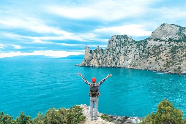 Glücklicher touristenmann mit rucksack mit erhobenen händen mit wunderschönem meerblick. sommerreisekonzept