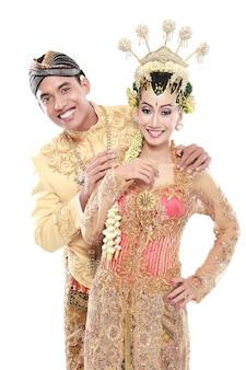 Glücklicher traditioneller java-hochzeitspaar ehemann und ehefrau umarmen sich