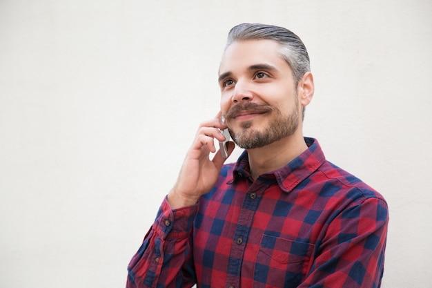 Glücklicher träumerischer mann, der am telefon spricht