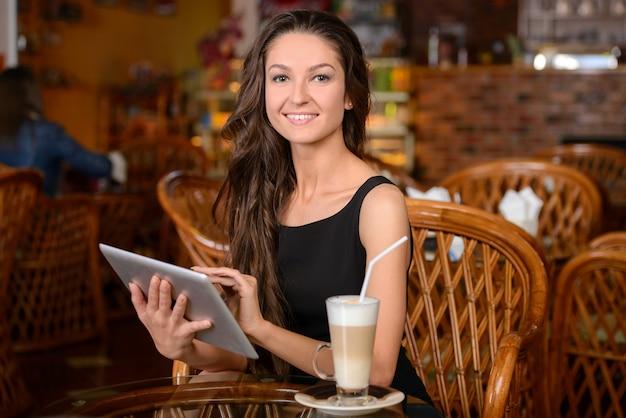 Glücklicher trinkender kaffee der jungen frau.