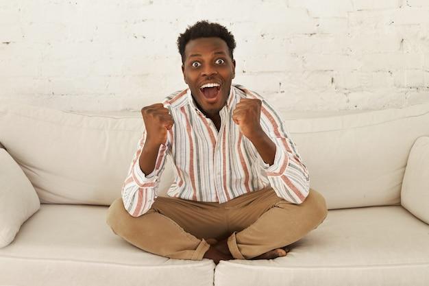 Glücklicher überglücklicher junger afrikanischer fußballfan, der spiel im fernsehen sieht, das tor feiert