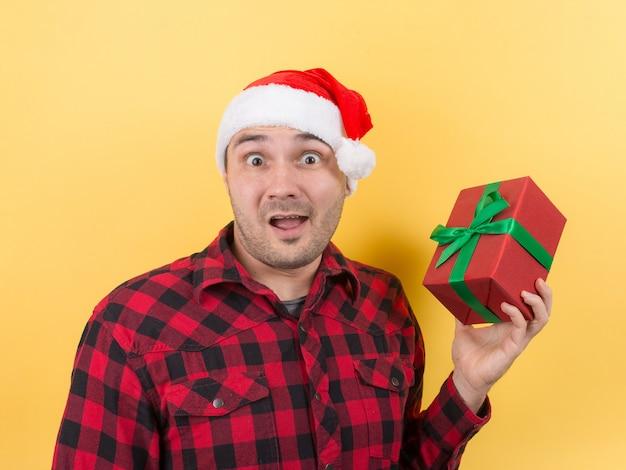 Glücklicher überraschter mann in einem roten hut, der ein geschenk mit bewunderung auf seinem gesicht hält