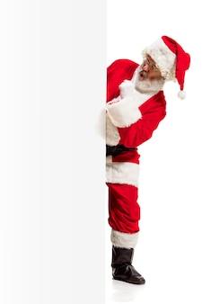 Glücklicher überraschter weihnachtsmann, der auf leeren werbebannerhintergrund mit kopienraum zeigt. lächelnder älterer mann, der am weißen rohling des leeren plakats zeigt