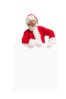 Glücklicher überraschter weihnachtsmann, der auf leeres werbebanner mit kopienraum zeigt