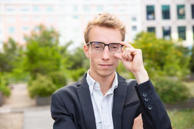 Glücklicher überzeugter geschäftsmann in den gläsern, die für kamera stehen