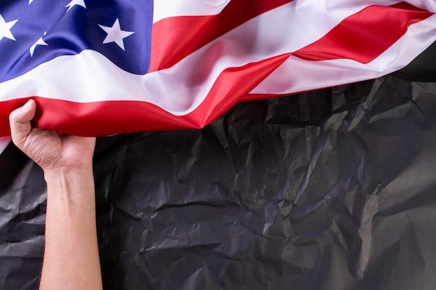 Glücklicher unabhängigkeitstag, gedenktag. mann, der amerikanische flaggen gegen einen schwarzen papierhintergrund hält.