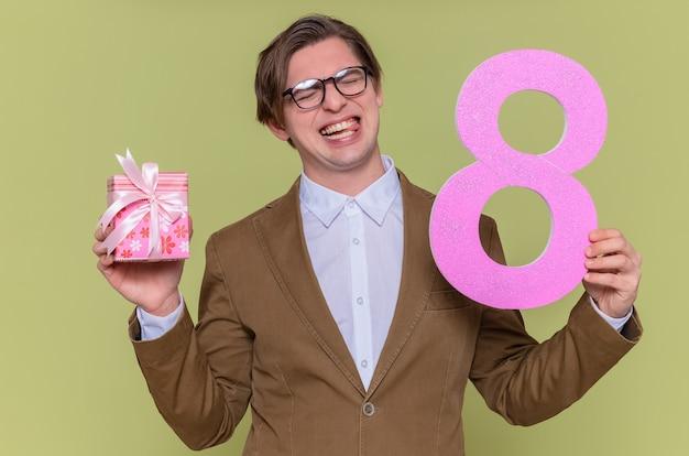 Glücklicher und aufgeregter junger mann, der eine brille trägt, die nummer acht hält, hergestellt aus pappe und geschenk, das fröhlich internationalen frauentag über grüner wand steht
