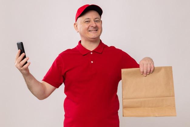 Glücklicher und aufgeregter lieferbote in roter uniform und mütze mit papierpaket und smartphone, der die kamera ansieht und selbstbewusst auf weißem hintergrund steht