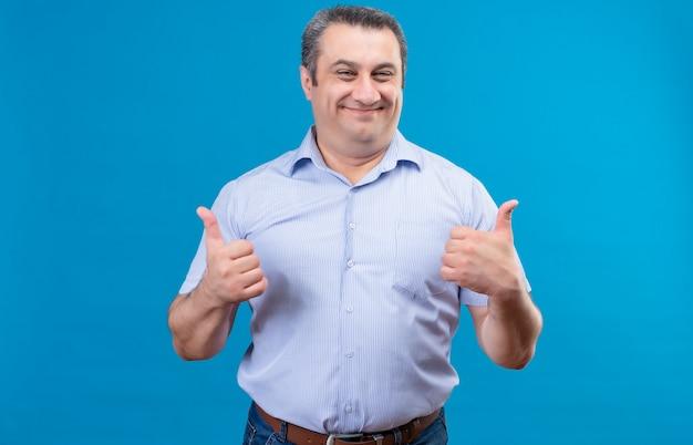 Glücklicher und aufgeregter mann mittleren alters im blauen hemd, der mit beiden händen daumen hoch wie geste auf einem blauen raum zeigt