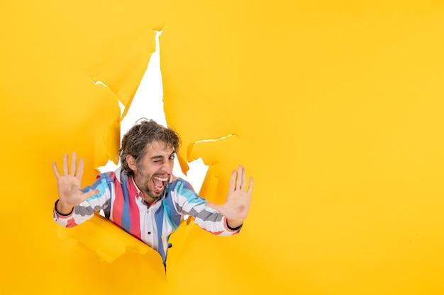 Glücklicher und emotionaler junger mann, der zehn im zerrissenen gelben papierlochhintergrund zeigt