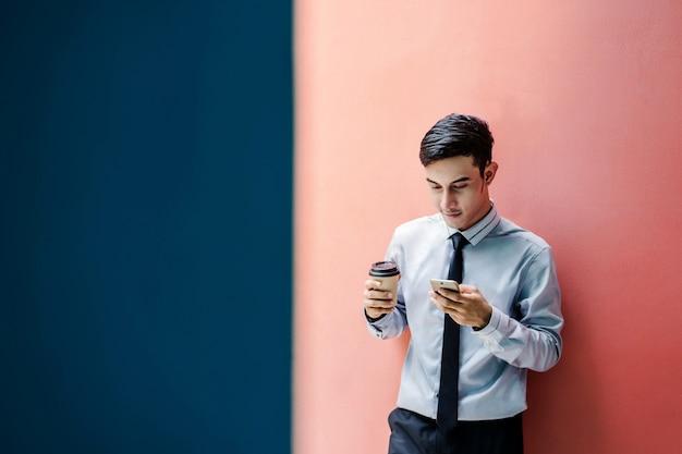 Glücklicher und freundlicher junger attraktiver geschäftsmann benutzen ein intelligentes telefon an der bunten wand