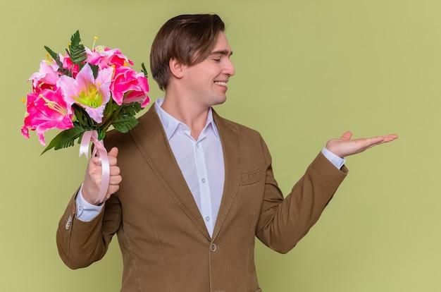 Glücklicher und fröhlicher junger mann, der blumenstrauß hält, der beiseite schaut lächelnd fröhlich präsentiert mit arm, der mit internationalem frauentagsmarschkonzept gratuliert