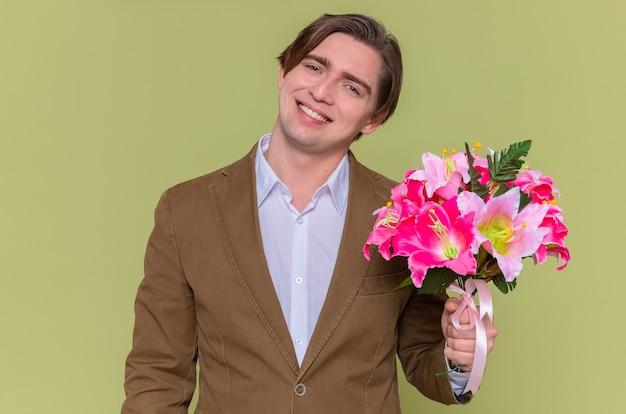 Glücklicher und fröhlicher junger mann, der blumenstrauß hält, der vorne lächelnd fröhlich geht, um mit internationalem frauentag zu gratulieren, der über grüner wand steht