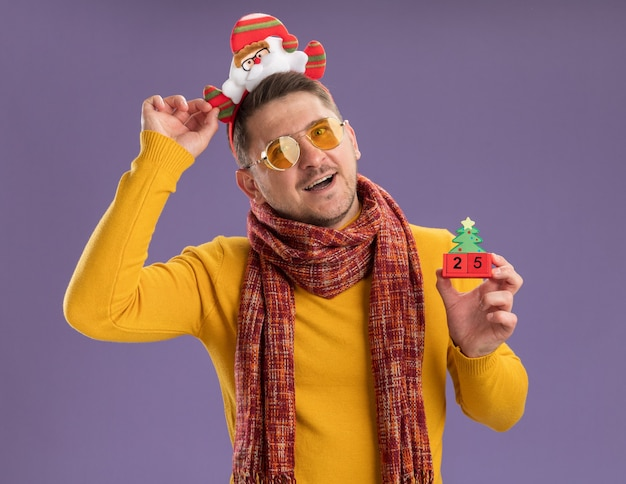 Glücklicher und fröhlicher junger mann im gelben rollkragenpullover mit warmem schal und brille, die lustigen rand mit weihnachtsmann auf kopf trägt, der spielzeugwürfel mit nummer fünfundzwanzig steht, die über lila wand stehen