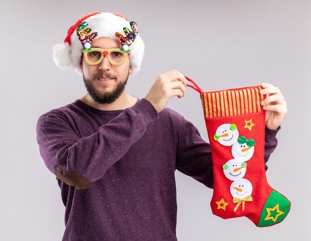 Glücklicher und fröhlicher junger mann im lila pullover und in der weihnachtsmannmütze, die lustige brillen hält, die einen weihnachtsstrumpf halten, der kamera betrachtet, die über weißem hintergrund steht