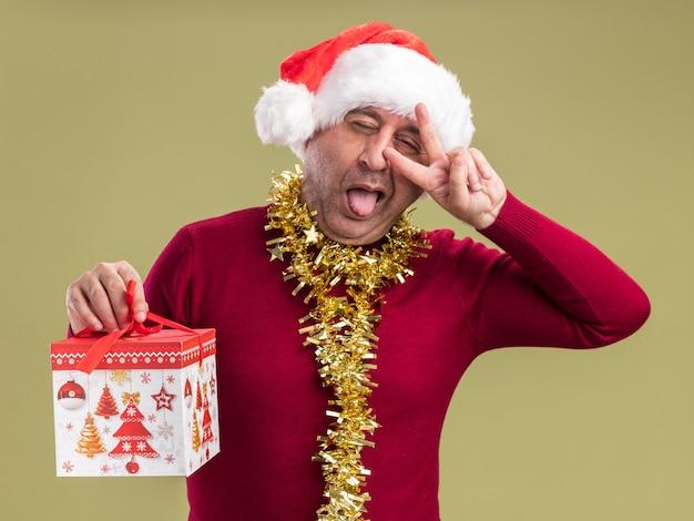 Glücklicher und fröhlicher mann mittleren alters, der weihnachtsweihnachtsmütze mit lametta um den hals hält, der weihnachtsgeschenk hält, das kamera betrachtet, die zunge herausragt, die v-zeichen zeigt, das über grünem hintergrund steht