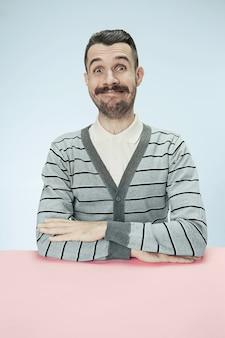 Glücklicher und lächelnder geschäftsmann, der am tisch auf blauem studiohintergrund sitzt.
