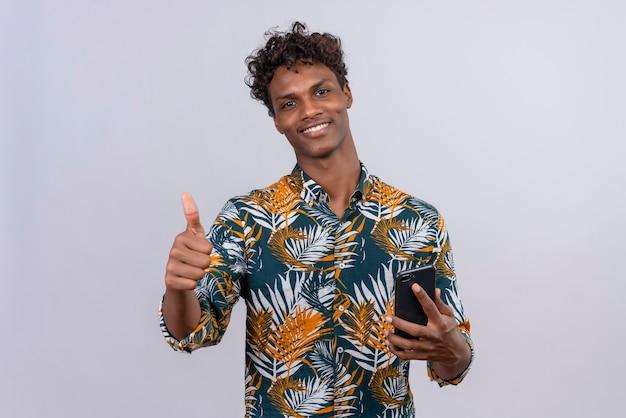 Glücklicher und lächelnder junger gutaussehender dunkelhäutiger mann mit lockigem haar im blatt bedruckten hemd, das handy hält, während mit daumen hoch zeichen aufwirft