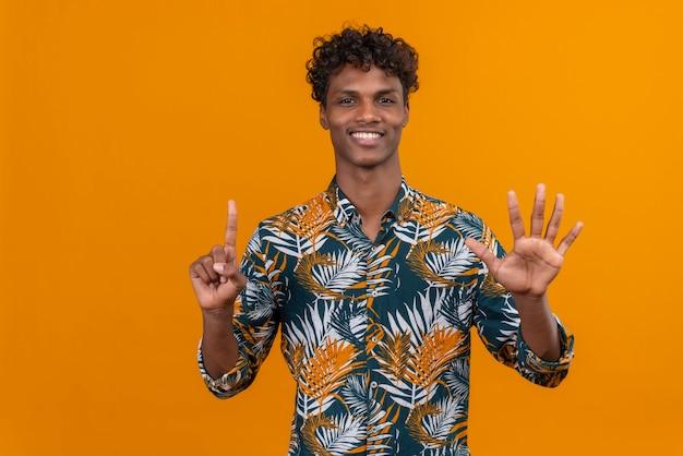 Glücklicher und lächelnder junger gutaussehender dunkelhäutiger mann mit lockigem haar im hemd mit blattdruck, während er mit den fingern nummer sechs zeigt
