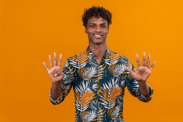 Glücklicher und lächelnder junger gutaussehender dunkelhäutiger mann mit lockigem haar im hemd mit blattdruck, während er mit den fingern nummer zehn zeigt
