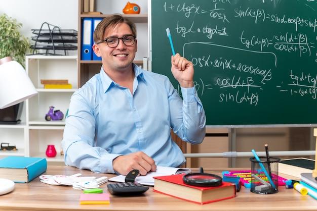 Glücklicher und lächelnder junger männlicher lehrer, der an der schulbank mit büchern und notizen sitzt, die bleistift vor der tafel im klassenzimmer halten
