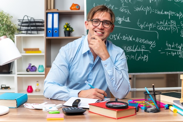 Glücklicher und lächelnder junger männlicher lehrer, der an der schulbank mit bücherstift und notizen vor der tafel im klassenzimmer sitzt