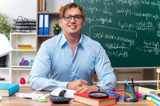 Glücklicher und lächelnder junger männlicher lehrer mit brille, der an der schulbank mit büchern und notizen vor der tafel im klassenzimmer sitzt