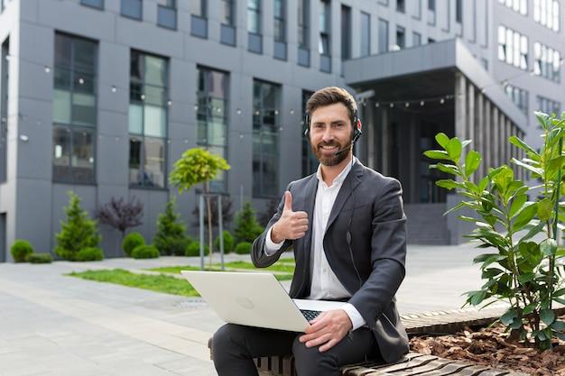 Glücklicher und lächelnder männlicher unternehmer, der die kamera mit video-headset betrachtet, positive unterstützung in kritischen situationen, diese unterstützung, mann, der im freien in der nähe des büros arbeitet