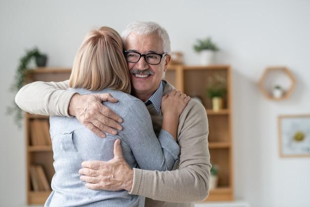 Glücklicher und liebevoller älterer mann, der seine blonde kleine tochter umarmt, während er liebe ausdrückt