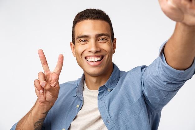 Glücklicher und netter freundlicher mann, der bestimmtheit sendet, kamera ausgedehnte hand hält und am smartphone lächelt, selfie nimmt, friedenszeichen macht, vlog aufzeichnet oder online mit freundin spricht,