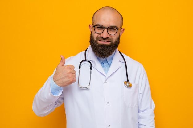 Glücklicher und positiver bärtiger arzt im weißen kittel mit stethoskop um den hals mit brille, der lächelnd mit daumen nach oben aussieht
