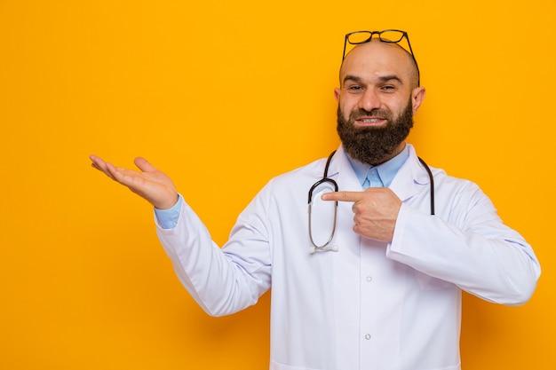 Glücklicher und positiver bärtiger mannarzt im weißen kittel mit stethoskop um den hals mit brille auf dem kopf, der etwas mit dem arm seiner hand darstellt, der mit zeigefinger zur seite zeigt
