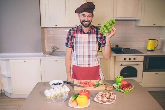 Glücklicher und positiver chef steht in der küche und schaut. er lächelt. junger mann hält letuce in der hand. er trägt pron. es gibt eier und gemüse am tisch.
