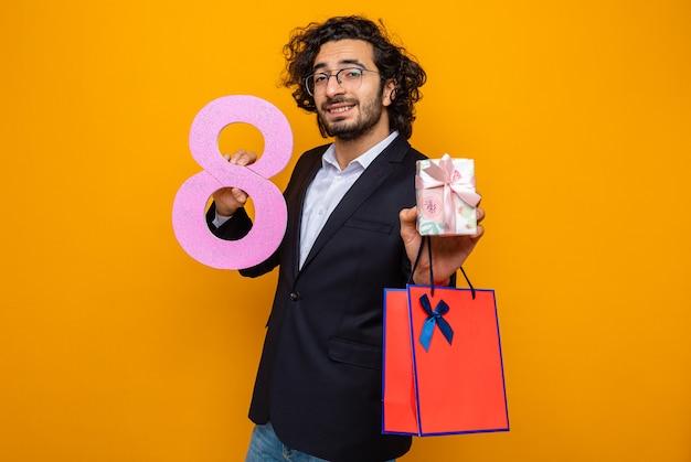 Glücklicher und positiver gutaussehender mann im anzug, der gegenwärtige papiertüte mit geschenk und nummer acht lächelt, die zuversichtlich feiern, internationalen frauentag 8. märz feiern