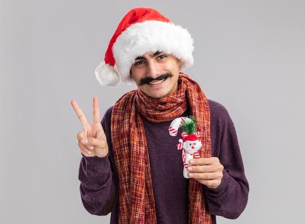 Glücklicher und positiver junger mann mit schnurrbart, der weihnachtsmann-weihnachtsmütze mit warmem schal um seinen hals trägt, der weihnachtliches zuckerstangen-lächelndes v-zeichen hält