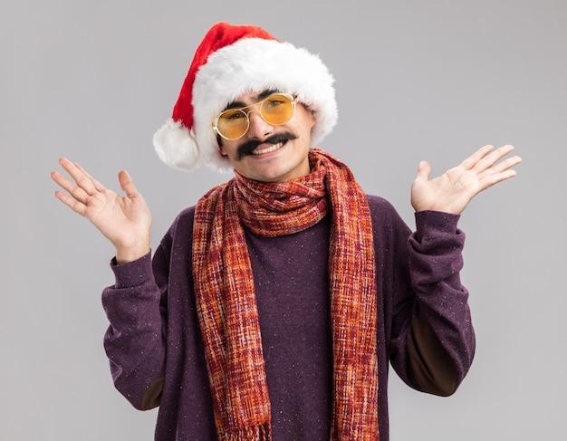 Glücklicher und positiver schnurrbärtiger mann mit weihnachtsmütze und gelber brille mit warmem schal um den hals, der fröhlich mit erhobenen armen über weißer wand lächelt