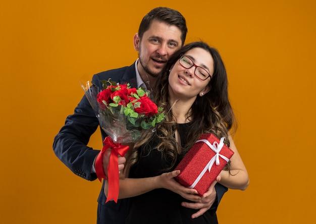 Glücklicher und schöner paarmann mit rosenstrauß und frau mit geschenk, das glücklich verliebt ist und den valentinstag über orangefarbener wand feiert