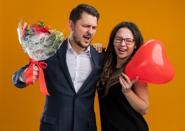 Glücklicher und schöner paarmann mit rosenstrauß und frau mit rotem ballon in herzform, die glücklich verliebt den valentinstag feiert
