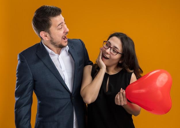Glücklicher und schöner paarmann und -frau mit rotem ballon in herzform, die spaß beim feiern des valentinstags haben