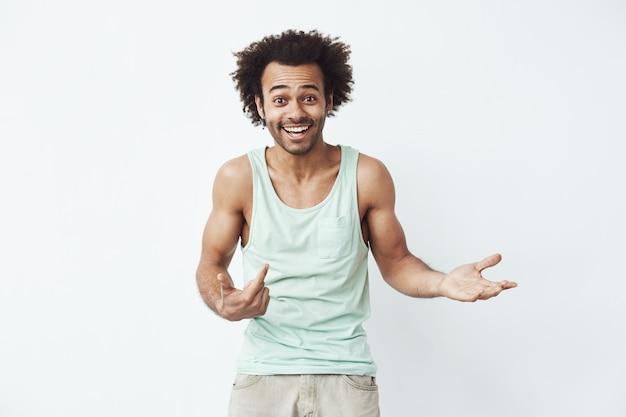 Glücklicher und selbstbewusster afrikanischer mann lächelnder zeigefinger auf sich selbst, der zu einer partei einlädt.